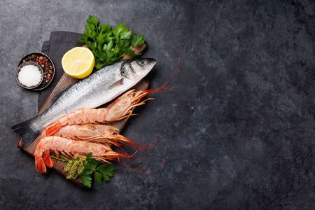 Fresh seafood. Trout fish and langostino shrimps with herbs and spices on a stone background. Top view flat lay. With copy space for text