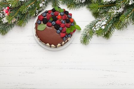 Christmas holiday chocolate cake or cheesecake with berries. On wooden table with copy space. Top view flat lay