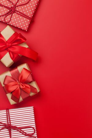 Christmas or Valentines day gift boxes on red background. Top view with copy space. Flat lay