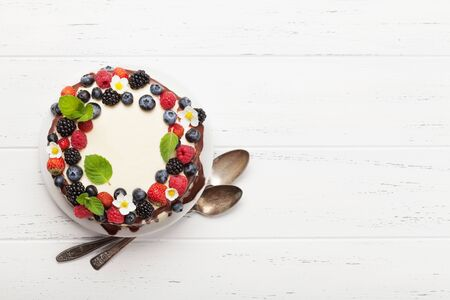 Chocolate cake or cheesecake with berries. On wooden table with copy space. Top view flat lay
