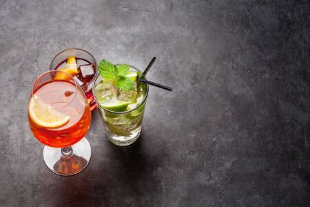 Three classic cocktail glasses on stone table.