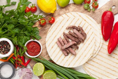 Mexican tacos with meat and vegetables cooking and ingredients