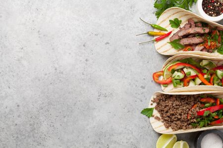 Set of mexican tacos with meat and vegetables in tortilla. Top view on stone table. Flat lay with copy space