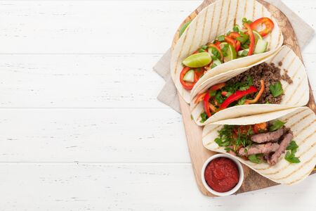 Mexican tacos with meat and vegetables in tortilla. Top view on wooden table with copy space Stock Photo