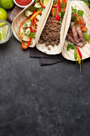 Set of mexican tacos with meat and vegetables in tortilla. And caipirinha cocktail. Top view on stone table. Flat lay with copy space