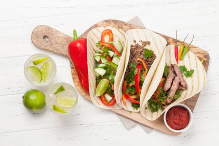 Set of mexican tacos with meat and vegetables in tortilla. And caipirinha cocktail. Top view on wooden table. Flat lay Stock Photo