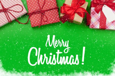 Christmas gift boxes on green background with xmas greeting. Top view