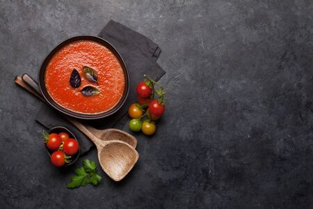 Tomato gazpacho soup on stone backdrop. Top view with copy space. Flat lay