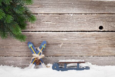 Christmas card with xmas decor and fir tree covered by snow in front of wooden wall. With space for your greetings