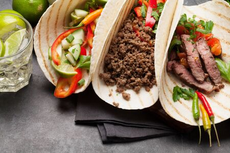 Set of mexican tacos with meat and vegetables in tortilla. And caipirinha cocktail Stock Photo