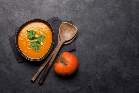 Pumpkin vegetable soup on stone backdrop. Top view with copy space. Flat lay