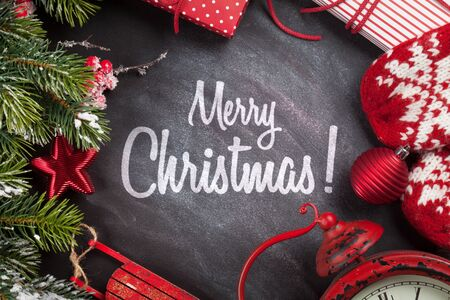 Christmas greeting card with gift box, decor and fir tree branch over blackboard texture background with xmas greetings