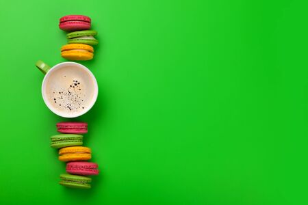 macaroon sweets and coffee on green backdrop. With copy space. Top view flat lay Banco de Imagens