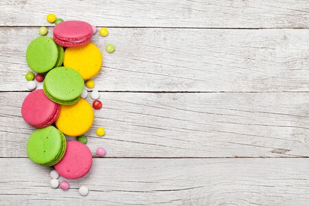 macaroon sweets on wooden backdrop. Top view flat lay with copy space Banco de Imagens