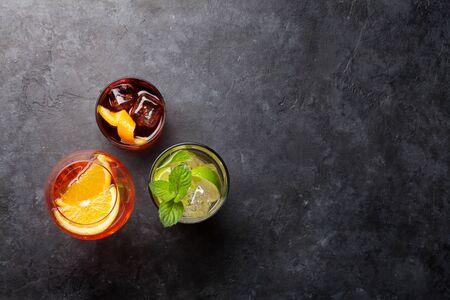 Tres copas de cóctel clásicas en la mesa de piedra.