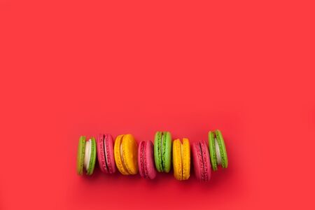 macaroon sweets on red backdrop. Top view flat lay with copy space Banco de Imagens