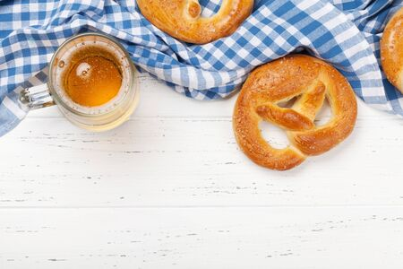Oktoberfest food backdrop. Pretzels and lager beer mug on white wooden background. Top view with copy space. Flat lay