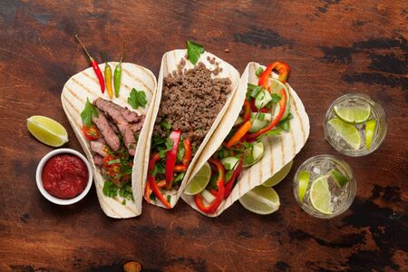 Set of mexican tacos with meat and vegetables in tortilla. Top view on wooden table. Flat lay with copy space Stock Photo