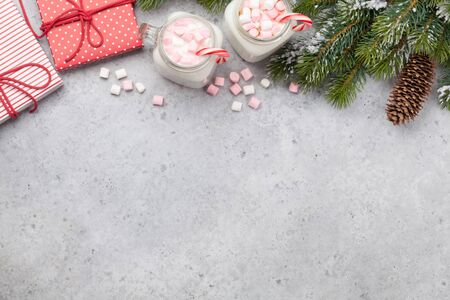 Traditional christmas cocktail with marshmallow. With gift boxes on stone table. Flat lay. Top view with space for your greetings