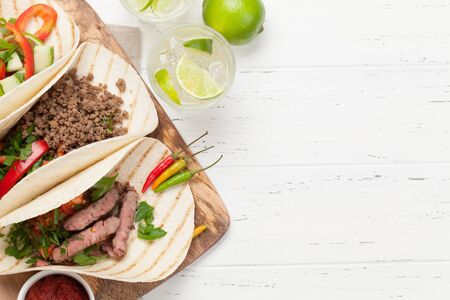 Set of mexican tacos with meat and vegetables in tortilla. And caipirinha cocktail. Top view on wooden table. Flat lay with copy space