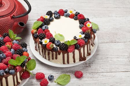 Chocolate cake and cheesecake with berries and tea. On wooden table with copy space Фото со стока