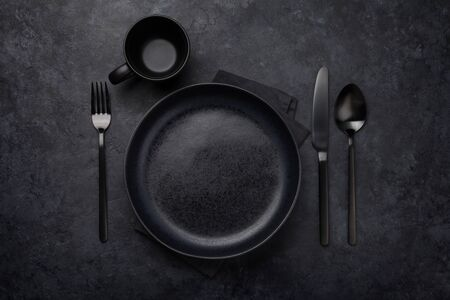 Empty plate, cup, fork and knife. Black kitchen utensils set on stone table. Top view flat lay with copy space