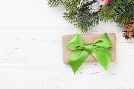 Christmas greeting card with gift box and fir tree branch over wooden texture background. Xmas backdrop. Top view with copy space for your greetings 版權商用圖片