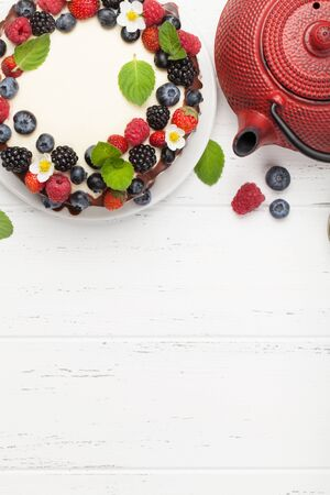 Chocolate cheesecake with berries and tea. On wooden table with copy space. Top view flat lay Фото со стока