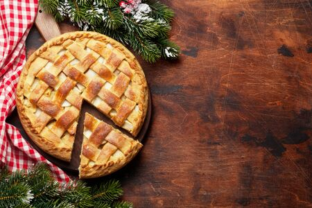 Christmas holiday greeting card with apple pie and fir tree. On wooden table with copy space. Top view flat lay