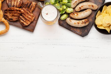 Oktoberfest set. Pretzels, sausages, meat and lager beer mug on wooden background. With copy space. Top view flat lay Stock Photo