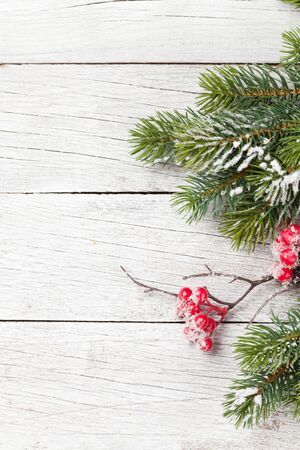Christmas greeting card with fir tree branch over wooden background. Xmas backdrop. Top view with copy space for your greetings