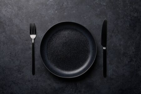 Empty plate, fork and knife. Black kitchen utensils set on stone table. Top view flat lay with copy space