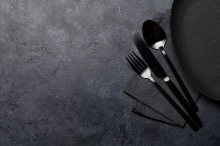 Empty plate, fork, spoon and knife. Black kitchen utensils set on stone table. Top view flat lay with copy space