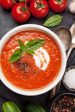 Cold gazpacho soup with ripe tomatoes, cucumber and basil on stone table. Top view flat lay Banque d'images
