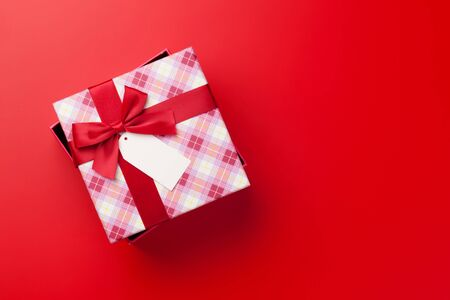 Christmas or Valentine's day gift box on red background. Top view with copy space. Flat lay