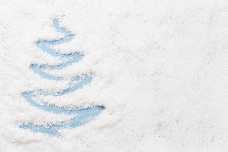 Christmas greeting card with fir tree shape and space for your xmas greetings over snow. Top view flat lay