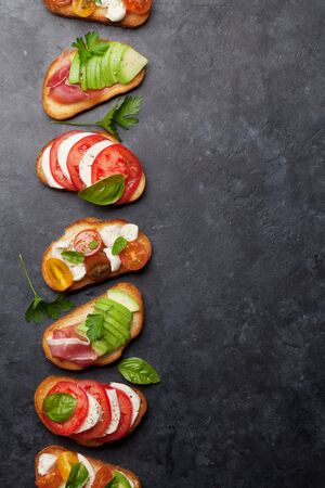 Traditional spanish tapas with tomatoes, mozzarella cheese, avocado and prosciutto on black stone background. Flat lay. Top view with copy space
