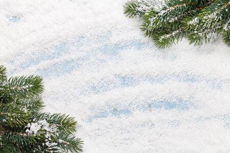 Tarjeta de felicitación de Navidad con rama de abeto sobre fondo de nieve. Telón de fondo de Navidad. Vista superior con espacio para tus saludos. Endecha plana