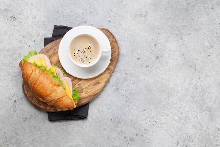 Coffee and croissant sandwich on stone table. French breakfast. Top view flat lay with copy space for your text Stockfoto