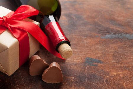 Valentines day greeting card with wine bottle, chocolate hearts and gift box on wooden background. With space for your greetings