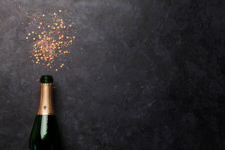 Plantilla de vacaciones de botella y dulces de champán. Telón de fondo de Navidad, cumpleaños o día de San Valentín. Vista superior con espacio para tus saludos.