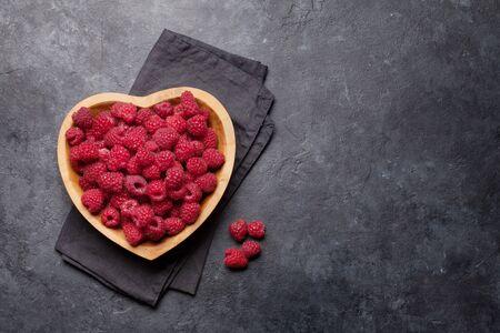 Framboise de jardin mûre fraîche dans un bol en forme de coeur sur une table en pierre. Vue de dessus avec espace de copie