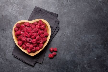 Fresh ripe garden raspberry in heart shaped bowl on stone table. Top view with copy space