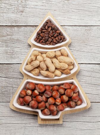 Christmas greeting card with various nuts in fir tree shaped box. Top view flat lay Standard-Bild - 133191078