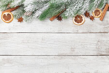 Christmas greeting card with fir tree and spices over white wooden background and copy space for your xmas greetings. Top view flat lay