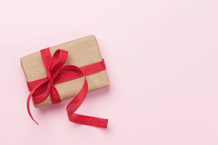 Christmas or Valentines day gift box on pink background. Top view with copy space. Flat lay