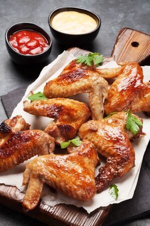 Hot barbecue chicken wings on wooden board with sauce