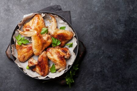 Hot barbecue chicken wings with sauce. Top view on stone table with copy space