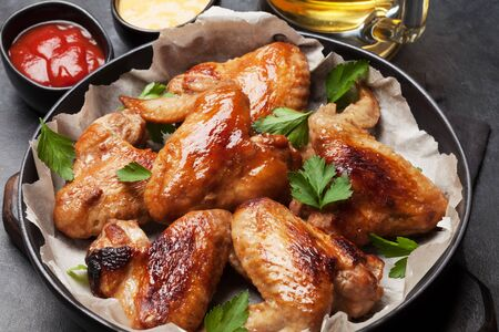 Hot barbecue chicken wings with sauce and draft beer