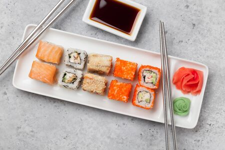 Japanese sushi set. Sashimi, maki rolls. On plate over stone background